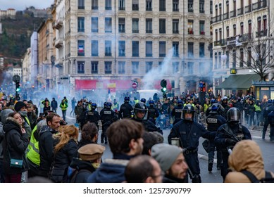 Lyon / France - December 08 2018: French riot police firing tear gas at Yellow Vests (Gilets Jaunes) protesters who are against fuel tax, government, and French President Macron