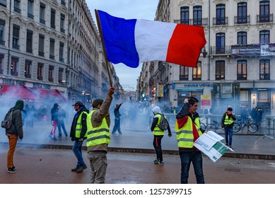 Lyon / France - December 08 2018: Yellow Vests (Gilets Jaunes), protest against fuel tax, government, and French President Macron. A protester was waving French flag in the scene.