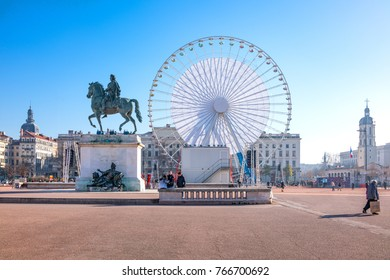 Lyon,  France - December 8, 2016:  Bellecour square with the equestrian monument of King Louis XIV and the big Ferris wheel in the background