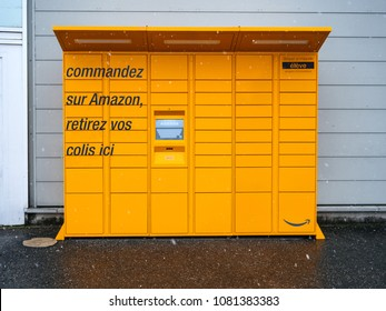 LYON, FRANCE - FEB 4, 2017: Front view of Amazon Locker orange delivery parcel package locker - self-service parcel delivery offered by online retailer Amazon.com snowy day