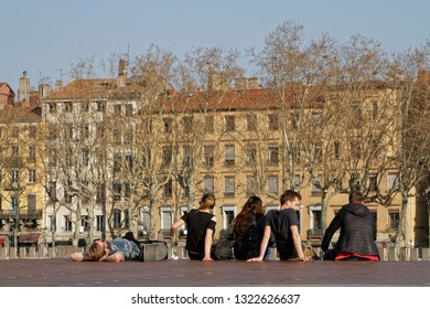 LYON, FRANCE, February 20, 2019 : A group of young people rest on the Saone river banks in Lyon city center on a sunny day.