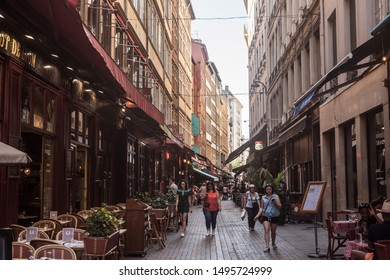 LYON, FRANCE - JULY 13, 2019: Tourists walking in Typical street of the Vieux Lyon (old Lyon) on the Presqu'ile district with tourists passing by near restaurants during a summer afternoon