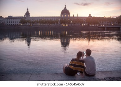 LYON, FRANCE - JULY 18, 2019: Couple, lovers, looking at a smarthone on the riverbank of the rhone, on the Quais De Rhone, facing Hotel Dieu, one of the main monuments of the city