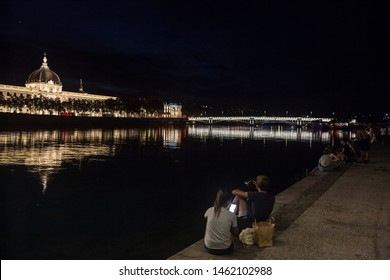 LYON, FRANCE - JULY 18, 2019: Couple, lovers, looking at a smartphone and taking pictures on the riverbank of the rhone, on the Quais De Rhone, facing Hotel Dieu, one of the main monuments of the city