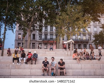 LYON, FRANCE - JULY 18, 2019: French people, mainly men sitting on the riverbank of the Rhone (quais) in the evening drinking alcohol while people are gathering for the tradition of apero