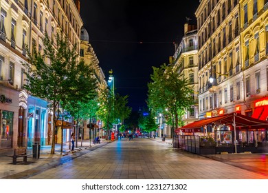LYON, FRANCE, JULY 22, 2017: Night view of people strolling through rue de la republique in the historical center of Lyon, France