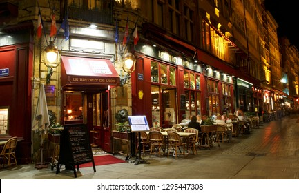 LYON, FRANCE - May 18, 2017: colorful Merciere street district in old Lyon, the famous old town of the city of Lyon by night. People on the terrace. Le Bistrot De Lyon restaurant.