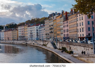 Lyon, France -- November 5, 2017 -- People, cars and colorful buildings on the bank of the Saone River in Lyon, France. Editorial Use Only.