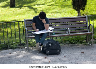 Lyon, France - October 14, 2017: Joe Zilsch, student prepares for classes on street sitting on bench, employee, state servant