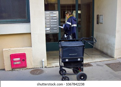 Lyon, France - October 14, 2017: Postman (postwoman, woman letter carrier) with mail bag in form of trolley