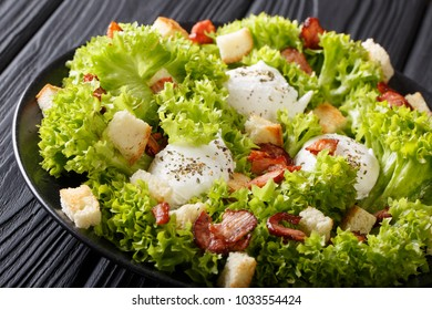 Lyonnaise salad made from lettuce, bacon, croutons and poached eggs close-up on a plate on a table. horizontal
