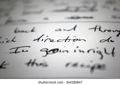 "Lyrics written in ink on paper, closeup/focus on the word ""direction"""