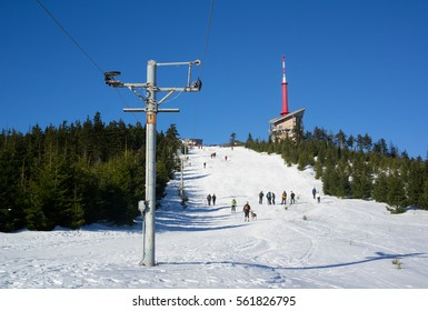 Lysa hora, Beskids mountains ( Beskydy ), Czech republic / Czechia, Central Europe - ski slope with ski tow. Unrecognizable tourists and building of transmitter in the distance.Sunny weather
