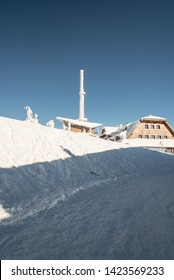 Lysa hora hill with communication tower and hut in Moravskoslezske Beskydy mountains in Czech republic during freezing winter day with clear sky