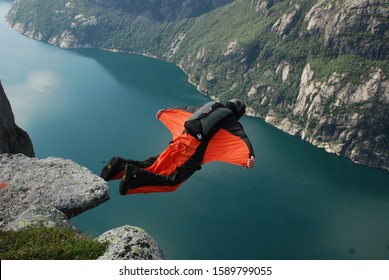 Lysebotn, Norway - 14,july,2010: Base jumper in red wingsuit flying down from one of the cliffs of Lysefiord. Kjerag mountain. Extreme sports.
