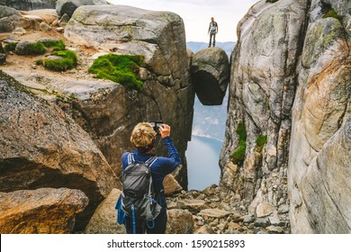 Lysefjorden, NORWAY - JULY 28, 2019: People taking picture on Kjerag or Kiragg (a giant boulder is wedged in a mountain crevasse) is a mountain in Forsand municipality in Rogaland county, Norway