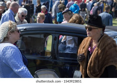 Lytham, Lancashire/UK - August 18th 2019: 1940s weekend, women dressed in period costume stood talking by a classic car with crowds of people in the background