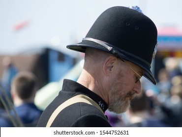 Lytham, Lancashire/UK - August 18th 2019: 1940s weekend, middle age caucasian man dressed as a 1940s policeman with blurred crowd of people in the background