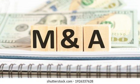 M and A. M A short for mergers and acquisitions. Business concept on wooden cubes and dollars background