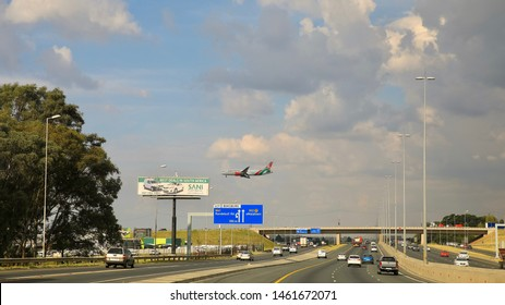 M12 Highway, Gauteng/South Africa - April 4, 2019 : Kenya Airways plane flying low over the highway, about to land at O.R. Tambo International Airport