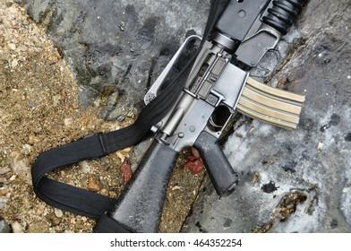 M16 rifle on rock background