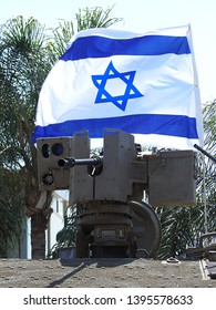 M2 Browning heavy machine gun .50 caliber (12.7 mm) mounted on Samson RCWS (Remote Controlled Weapon Station) of armored vehicle of the Israel Defense Forces with a waving Israeli flag in background