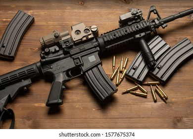 m4 rifle with optical sight, ammunition and cartriges on wooden table