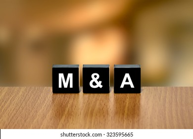 M&A or merger and acquisition on black block with blurred background