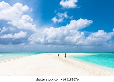 MAAFUSHI, MALDIVES - FEBRUARY 29, 2016: Amazing clouds during sunny day in a sandbank close to Maafushi in Maldives with few people