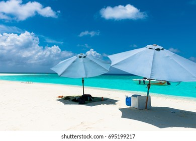 MAAFUSHI, MALDIVES - FEBRUARY 29, 2016: Two umbrellas during sunny day in a sandbank close to Maafushi in Maldives with turquoise water