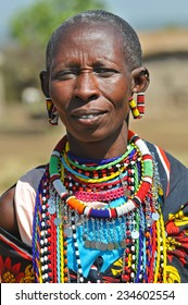 MAASAI MARA, KENYA - AUGUST 12: Maasai Woman in the village, 12 August, 2010 at Masaai Mara, Kenya. The Maasai are the most famous tribe in Africa. They are nomadic and live in small villages.