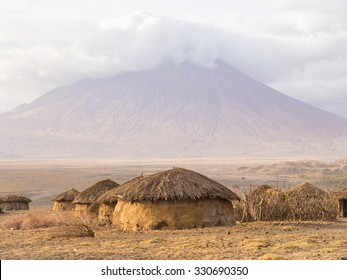 Maasai village in front of the Ol Doinyo Lengai (Mountain of God in the Maasai language), an active volcano in Arusha Region i the Northern Tanzania, Africa, at sunrise.