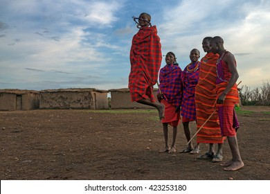 MAASAI VILLAGE, KENYA - JANUARY 2 2015: Tourists visit maasai village near Maasai Mara. Watching traditions of local tribes is one of the most popular attraction for tourists who come to Kenya.