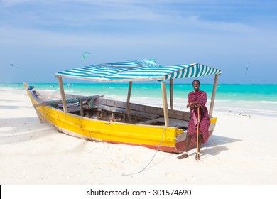 Maasai warrior lounging aroundon traditional colorful wooden boat on picture perfect tropical sandy beach on Zanzibar, Tanzania, East Africa. Kiteboarding spot on Paje beach.