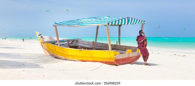 Maasai warrior lounging aroundon traditional colorful wooden boat on picture perfect tropical sandy beach on Zanzibar, Tanzania, East Africa. Kiteboarding spot on Paje beach.