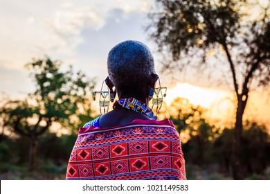 Maasai woman with beautiful clothing and jewellery and African sunset
