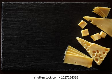 Maasdam, emmental and appenzeller cheese slices isolated on black background