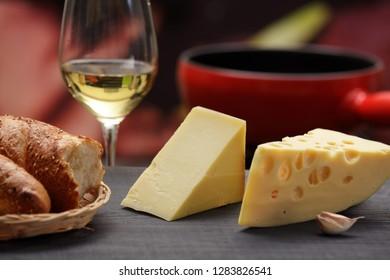 Maasdam and emmental cheese wedges, white wine glass, fondu