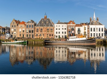 Maassluis, The Netherlands - February 26, 2019: the harbor of Maassluis with old boats, tugs and monumental houses on a sunny day.