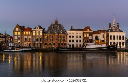 Maassluis, The Netherlands - February 26, 2019: the harbor of Maassluis with old boats, tugs and monumental houses at night.