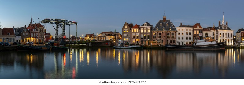 Maassluis, The Netherlands - February 26, 2019: Panorama of the harbor of Maassluis with old boats, tugs and monumental houses at night.