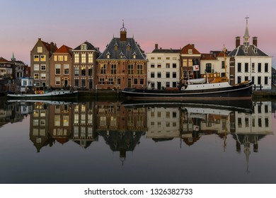 Maassluis, The Netherlands - February 26, 2019: the harbor of Maassluis with old boats, tugs and monumental houses on a eveniung with sunset.