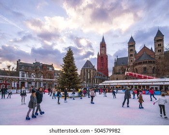 Maastricht, Holland, December, 2014: People skating on the Ice-rink at the Christmas market on the Vrijthof