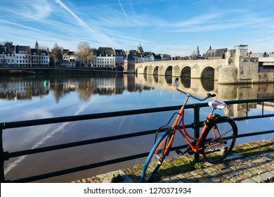 MAASTRICHT, NETHERLANDS - 26 December 2018: Bikes sit on the rioverbank with St Servaas Bridge in the background, Maastricht on a sunny day
