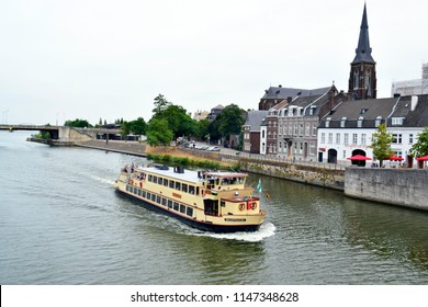 MAASTRICHT, NETHERLANDS - August 01, 2018: Tourists on the boat trip and buildings near river Meuse in city center ,this place is one of the famous tourist destination in Maastricht, Netherlands.