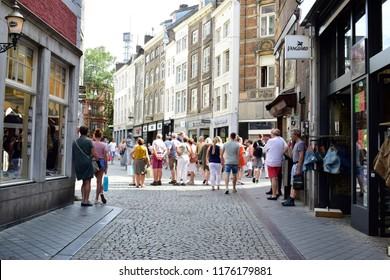 MAASTRICHT, NETHERLANDS - August 01, 2018: Crowd of tourist looking something on sidewalk and enjoy shopping in street center ,this place is one of the famous shopping center in Maastricht,Netherlands