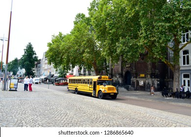 MAASTRICHT, NETHERLANDS - August 01, 2018: City-Tours Maastricht bus or yellow school bus parked on the sidewalk and waiting for tourist who want to go visit or travel around Maastricht city.