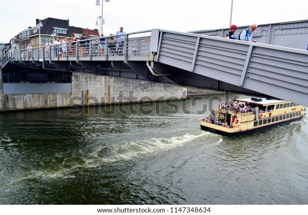 MAASTRICHT, NETHERLANDS - August 01, 2018: The boat trip passes under the bridge over river Meuse and tourists sit on the boat for visit the city or travel in holiday time.