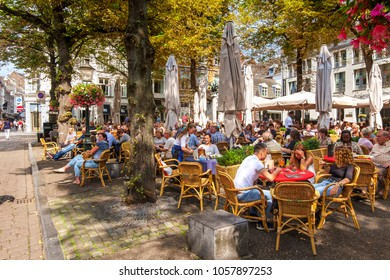 Maastricht, Netherlands, August 2015. People enjoying a drink on ta terrace, under the trees in summer