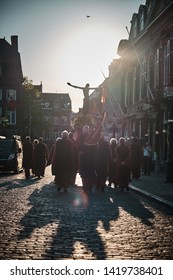 Maastricht, Netherlands - June 9, 2019: Religious procession with a congregation carrying a statue of Jesus Christ through the street of Maastricht. Backlit shots.